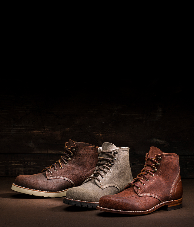 Path less traveled boot collection on a wooden background