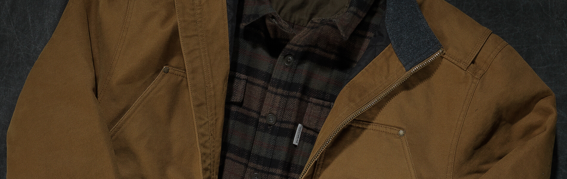Brown jacket with green plaid shirt.