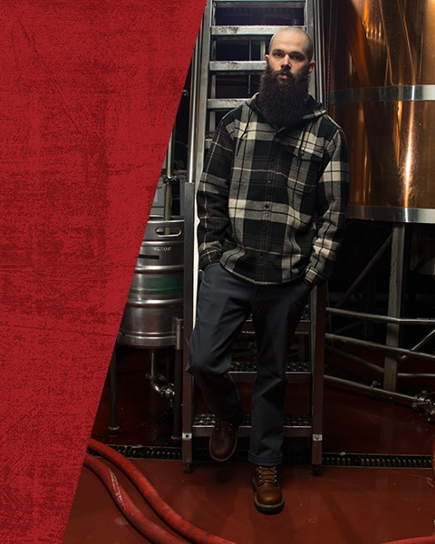 Man wearing a Wolverine plaid hoody and Wolverine boots, standing in front of some brewing tanks.