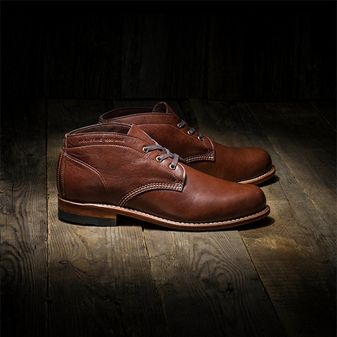 A pair of brown 1000 Mile chukka boots on a hardwood floor