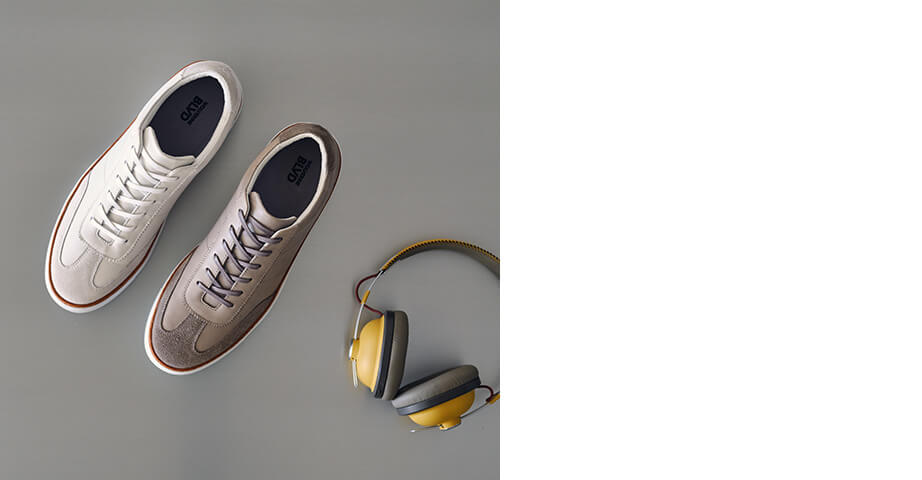 Wolverine BLVD Court sneakers in a variety of colors beside a pair of noise-canceling headphones.