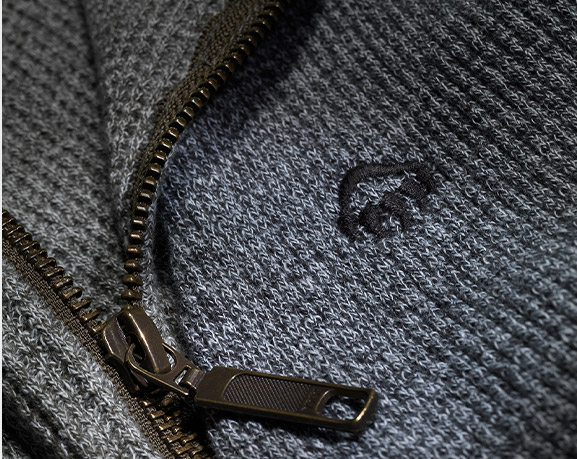Close up of a grey knit sweater displaying black Wolverine logo and black zipper.