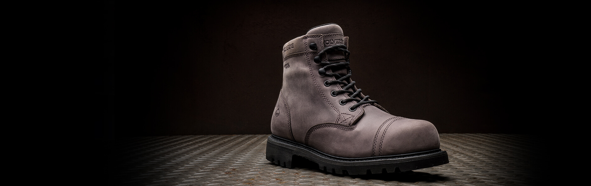 A grey Journeyman boot stands on a reinforced steel platform against a dark background.