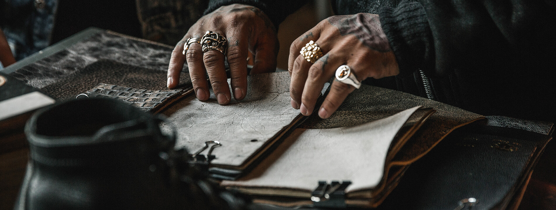 A man's weathered and tattooed hands, wearing chunky rings are leafing through a variety of leathers.