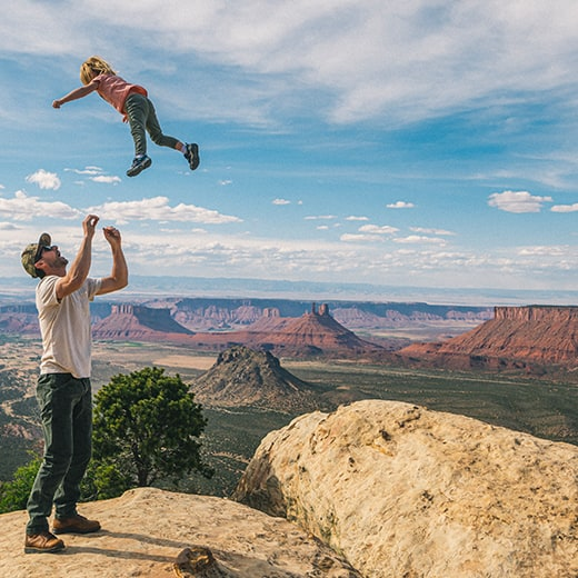 Man throwing a kid up in the air, with a backdrop of southwest mountains.