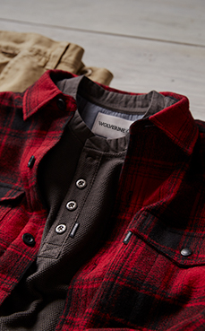 Red plaid collared shirt over grey T and tan pants.