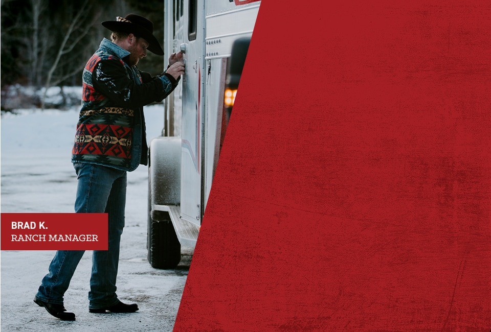 Brad K., Ranch Manager. Brad is closing the door of a horse trailer.