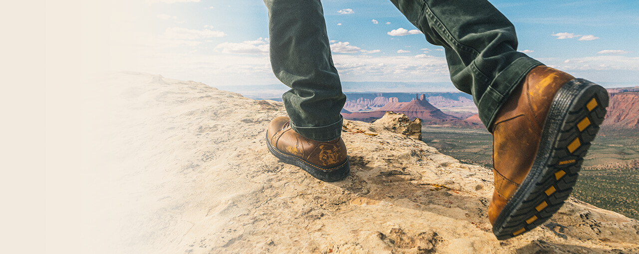 Person walking on a mountain wearing Hellcat UltraSpring Wedge boots.