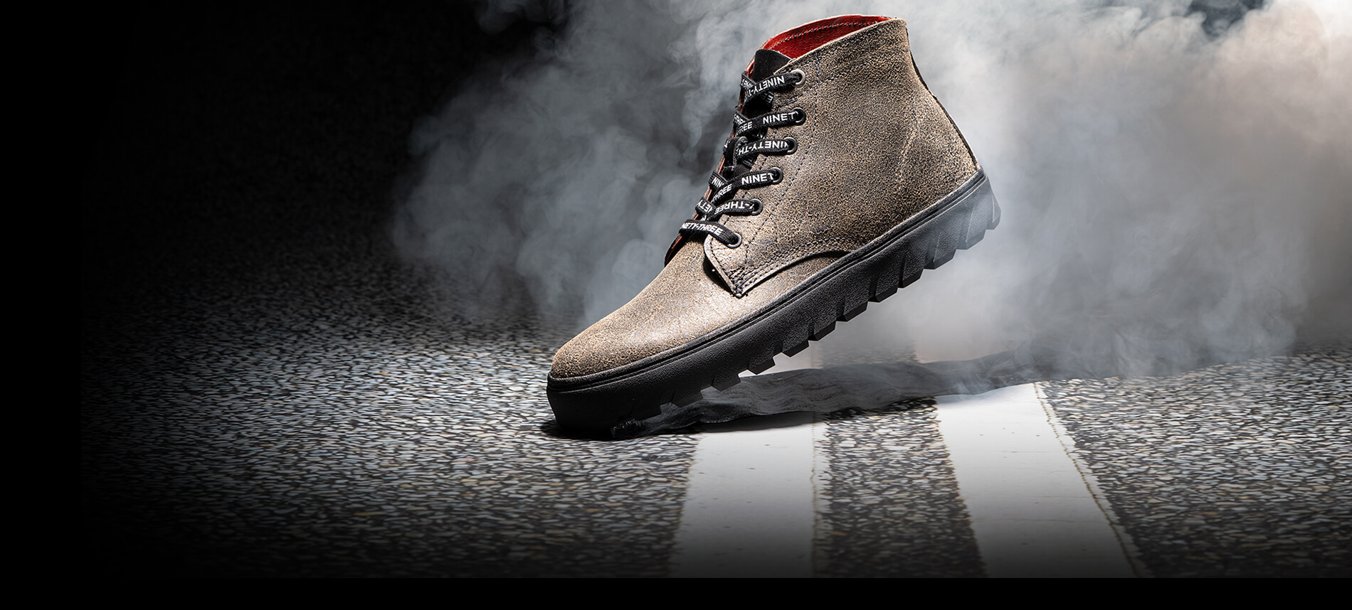 Brown with black sole 1000 Mile Combat Boot in a cloud of white smoke.
