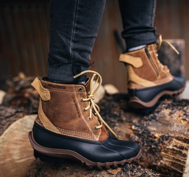 Person wearing Wolvering Torrent boots, standing on logs.