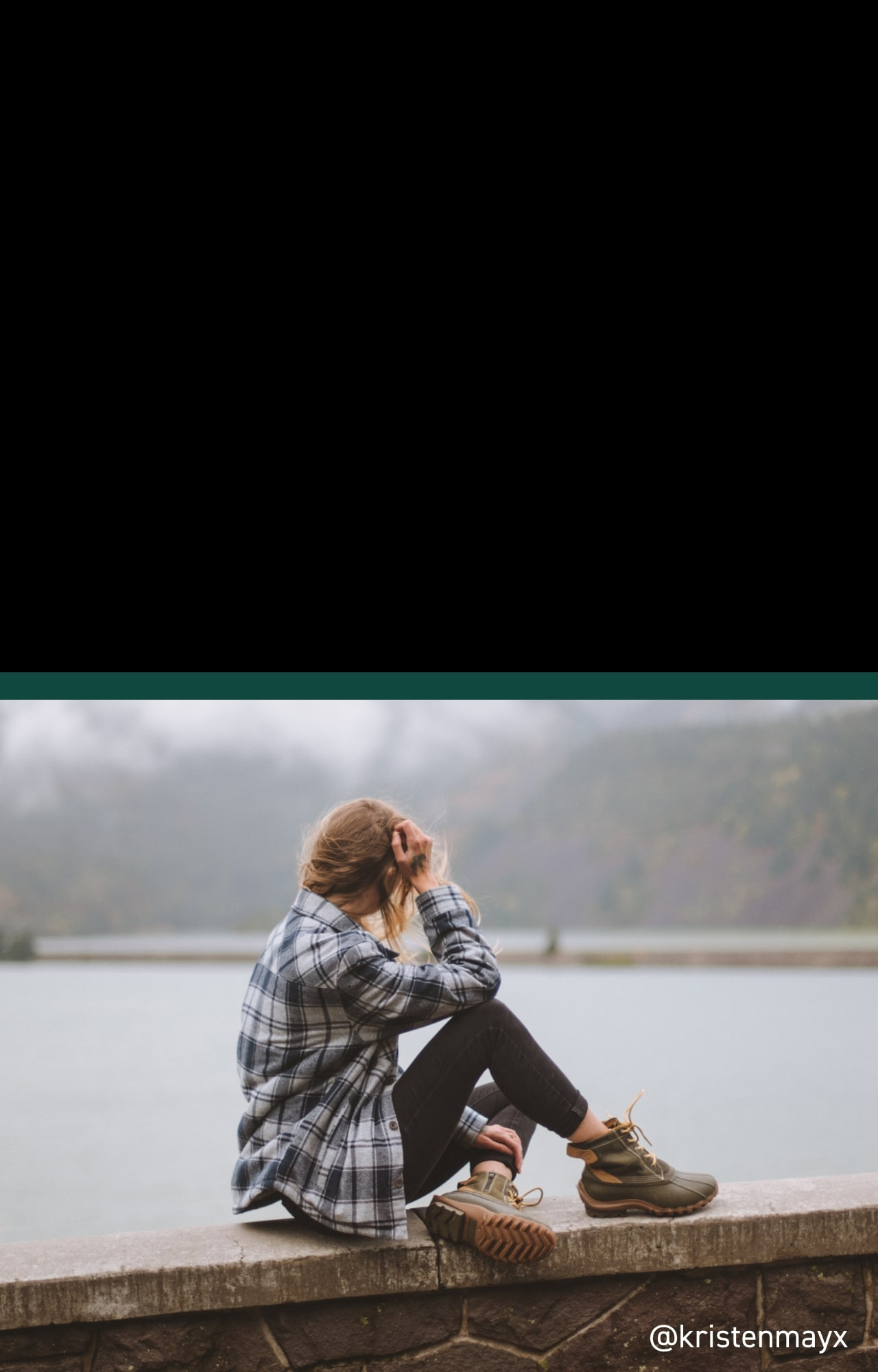 Person wearing Torrent boots sitting on a ledge overlooking a lake.