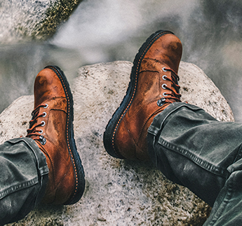 Person wearing boots sitting on a cliff.