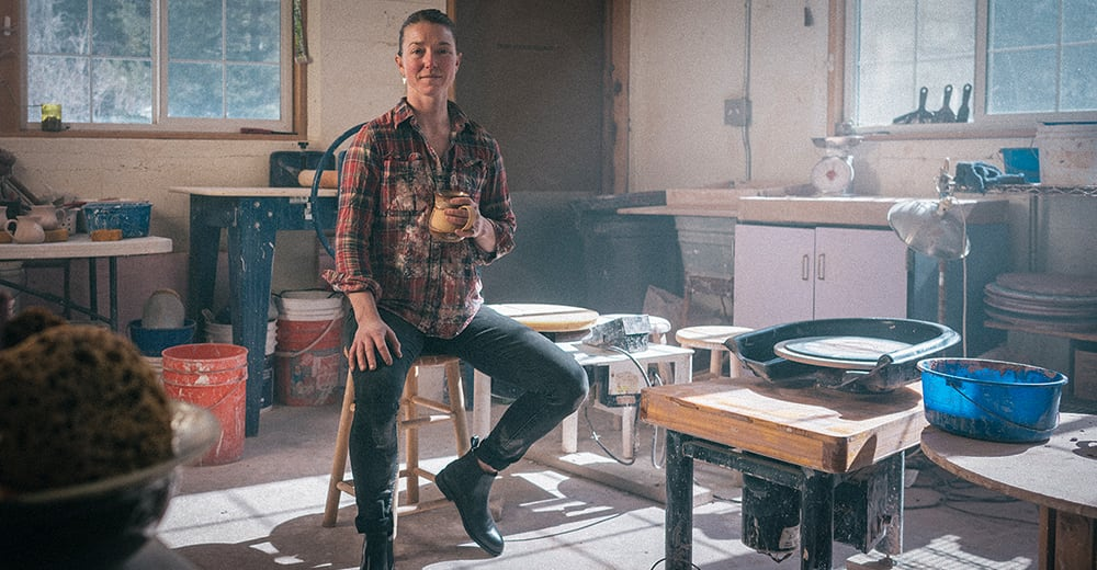 Kim H. sitting on a stool in her pottery studio, wearing black BLVD Chelsea boots.