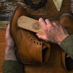 Man brushing leather boot