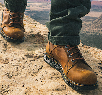 Person with boot walking on a mountain.